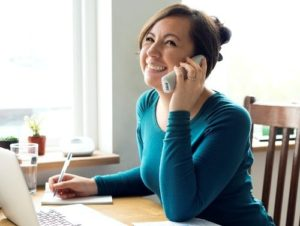 Smiling person on the phone and taking notes