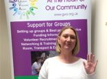 Mandy Bright raising a hand for International Women's Day 2021, in front of GVA's banner