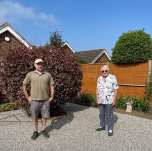 Gareth with one of his happy customers, both standing in the garden